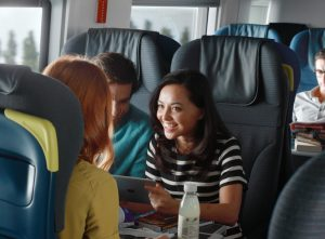 Happy passengers on a train looking at an iPad