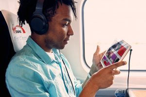 Man on train looking at tablet